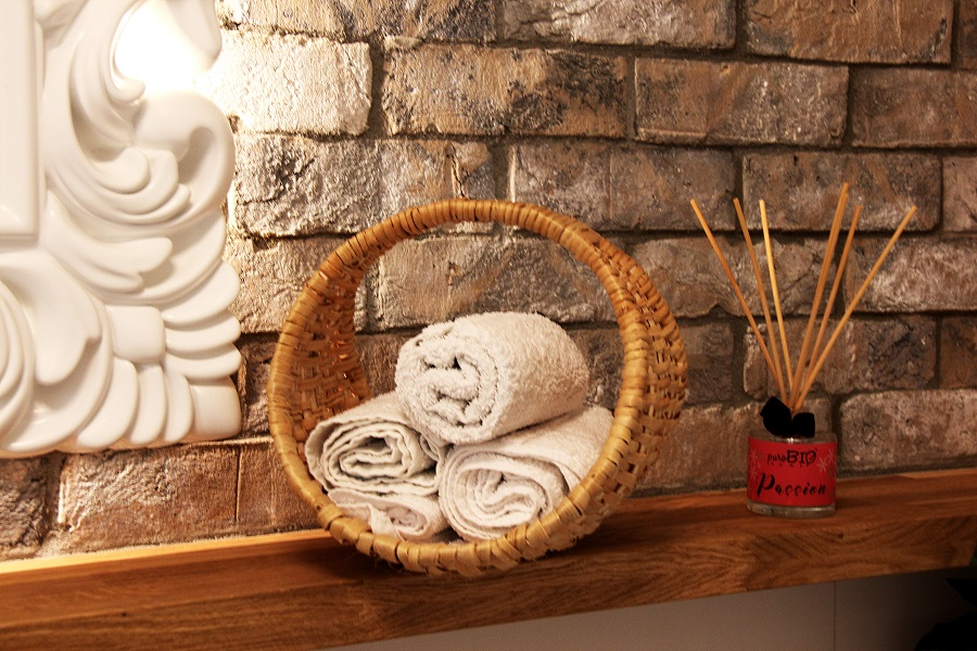 wickerworks made of a pine root in the bathroom with classic elements - spare towels in the basket