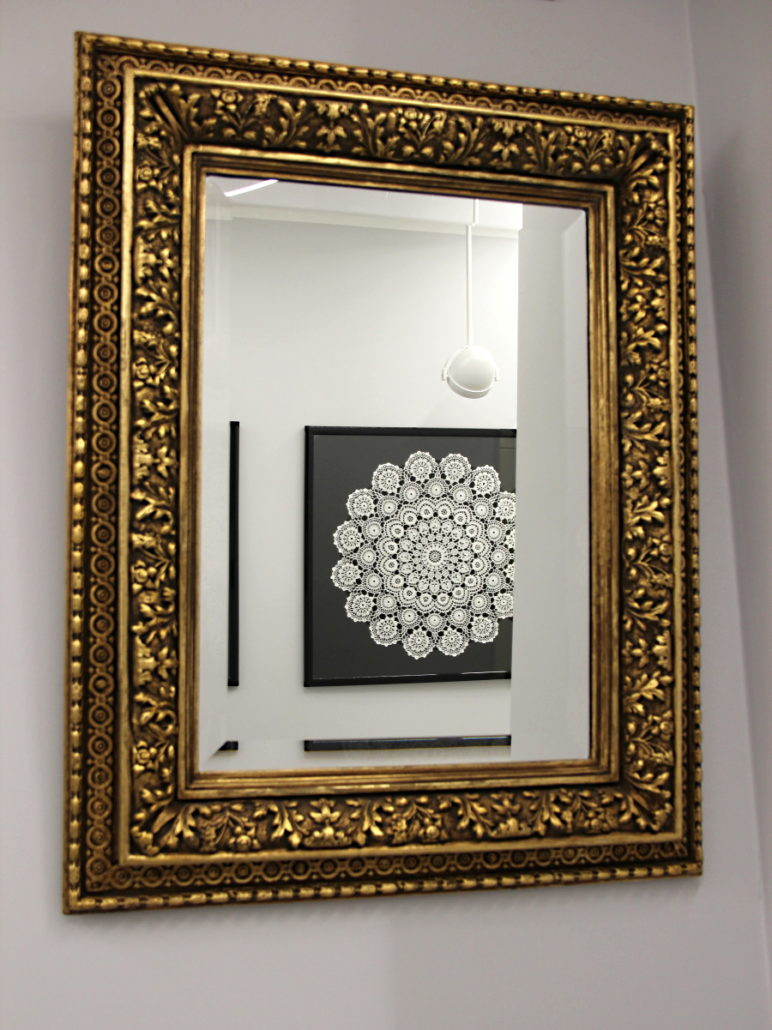 a framed Koniakow lace reflected in amirror