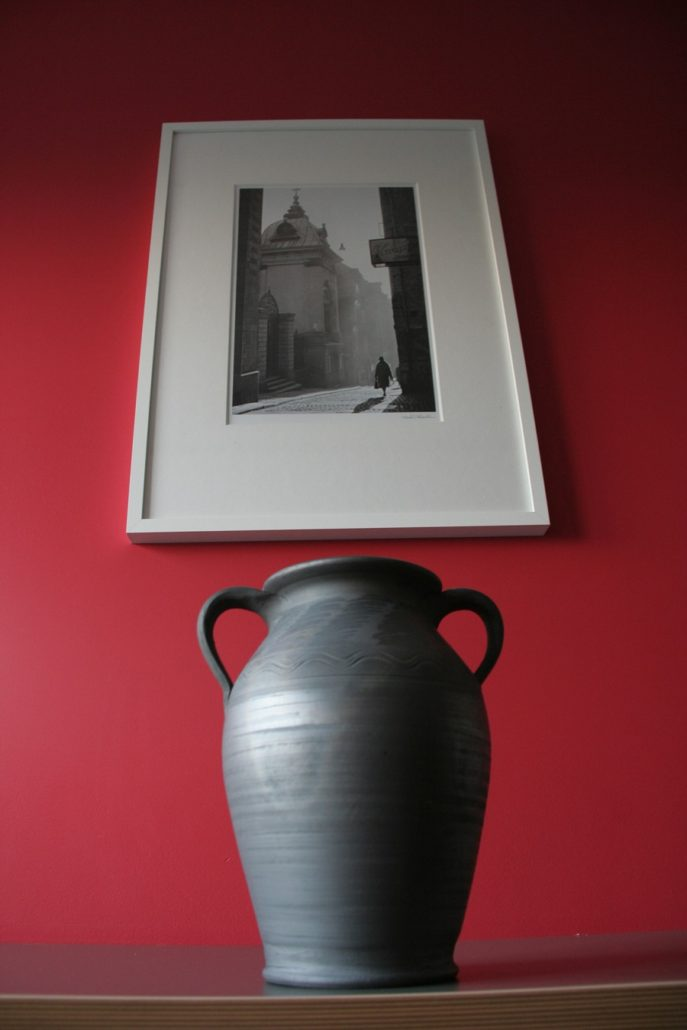 grey pottery – apot with acharacteristic silver color look beautiful against the red wall
